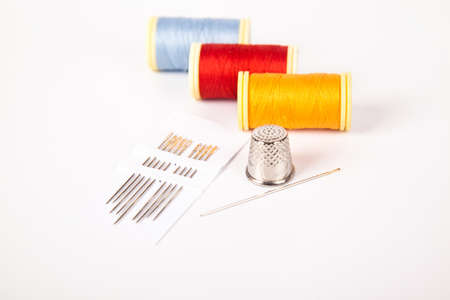 Sewing supplies concept, colorful threads needle and thimble, isolated on white background