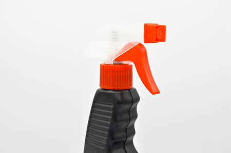 Black orange colored plastic spray detergent bottle, cosmetic container, isolated on white background