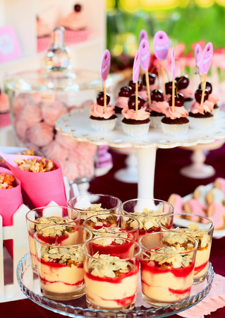 Delicious sweet buffet with cupcakes, tiramisu glasses and other desserts photo