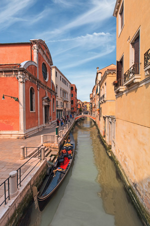 Traditional gondola parked in narrow venetian canal photo
