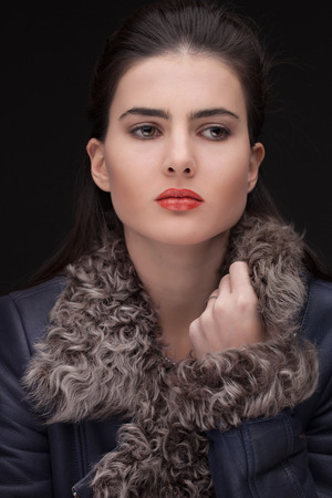 furskin: Young white female updo hairstyle on dark background, looking aside