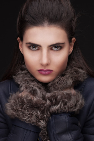 furskin: Young white female updo hairstyle on dark background, hooded look