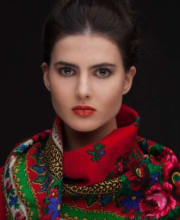 updo: Young female in russian traditional red shawl, updo hairstyle on dark background