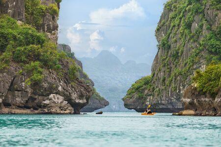 ocean kayak: Kayak amarillo en el agua de mar de color turquesa entre las rocas de la bah�a de Halong