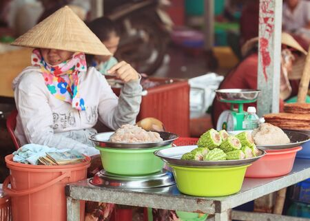 conical: Traditional asian market stall with traditional dishes and seller in conical hat Stock Photo
