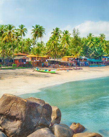 downshift: Beautiful Goa province beach in India with fishing boats and stones in the sea