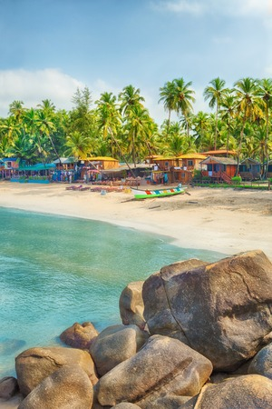 beach paradise: Beautiful Goa province beach in India with fishing boats and stones in the sea