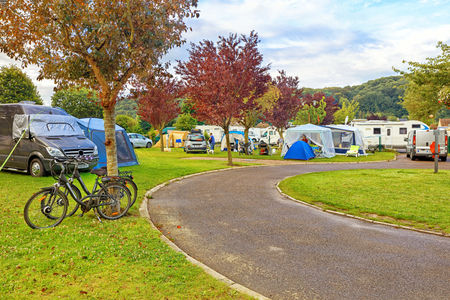 Green camping loan in Europe with vehicles and tents Stock Photo