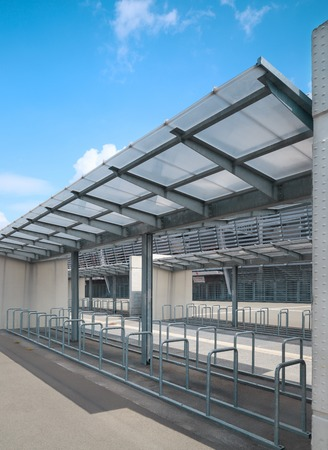 Metal railings of bicycle parking lot with glass canopy