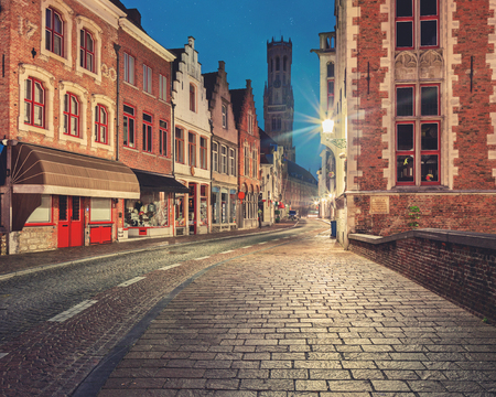 Traditional medieval red and white brickwall architecture of Bruges at twilight with  Belfort on background Stock Photo