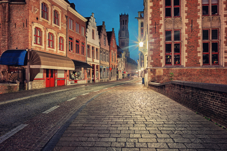 belfort: Traditional medieval red and white brickwall architecture of Bruges at twilight with  Belfort on background Stock Photo