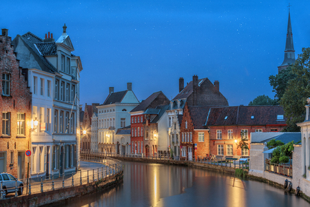 pitched roof: glowing lights in dusk of medieval Bruges old town, Belgium Stock Photo
