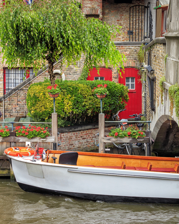 boat dock: Tourist boat wating tourists on medieval canal of Bruges