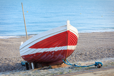 red pebble: seaside shot. Red boat on the pebble beach