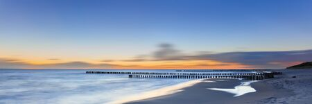 gentle dream vacation: Wooden piles dipping into the ocean on sandy beach at sunset. Hel Peninsula, Baltic sea, Poland