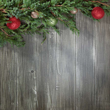 new year background: Christmas background with glowing colorful balls and green pine tree on old wooden board