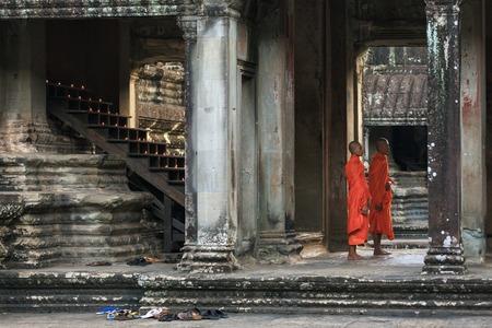 december 21: Angkow Wat temple, Siem Riep, Cambodia - December 21, 2014: Budhist monks praying in sunlit Angkor Wat temple gallery