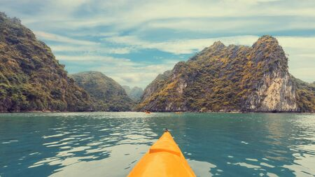 ocean kayak: Yellow kayak on turquoise sea water amongst the rocks of Halong Bay. Creative effect panorama