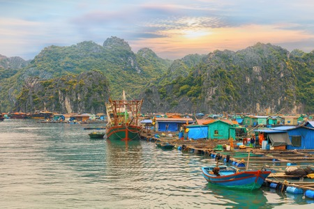 vietnam: Traditional asian floating village of Halong Bay at sunset, Vietnam