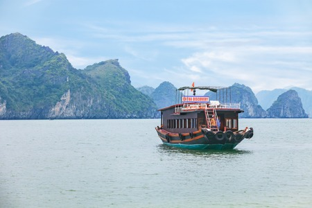cat island: Halong Bay, Vietnam - December 17, 2014: cruise boat sailing among the rocks of Cat Ba island Editorial