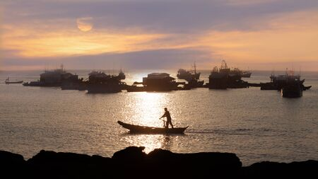fishing industry: Dramatic sunset in the ocean. silhouettes of traditional asian fishing boats and fisherman