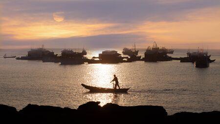 pescador: espectacular puesta de sol en el oc�ano. siluetas de los barcos de pesca tradicionales de Asia y pescadores