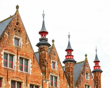 pitched: Traditional medieval red brickwall architecture of Bruges isolated on white background