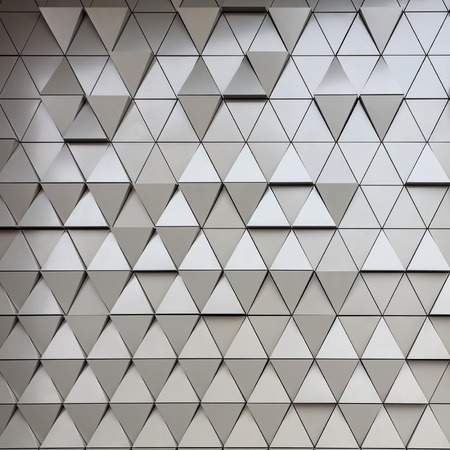 building material: Abstract close-up view of modern aluminum ventilated triangles on facade