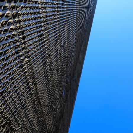 Abstract view of modern perforated metal facade wall on sky background