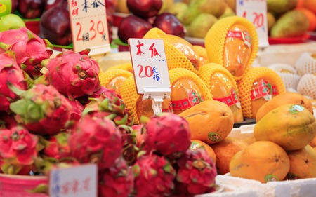 Traditional asian market stall full of fresh dragon fruits and papayas