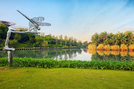 Singapore, Republic of Singapore - May 5, 2016: Gardens by the Bay, Marina Bay Sands hotel and Dragonfly scultpure reflecting in lake at sunrise Editorial