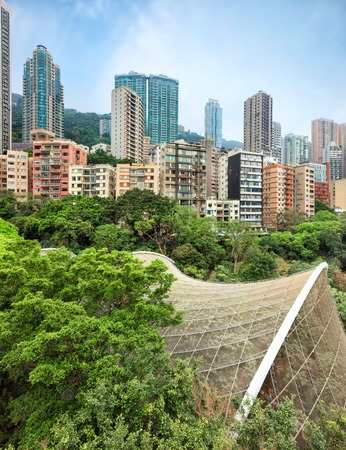 View on residential area of Hong Kong with high-rise apartment buildings rising over Hong Kong Park with Edward Youde Aviary dome of birds exibition