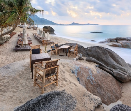 downshift: Empty morning Samui beach with beach tables on foreground