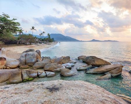 downshift: Empty morning Samui beach with beach rocks on foreground