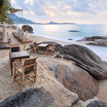 Empty morning Samui beach with beach tables on foreground