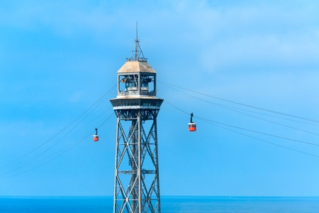 montjuic: Red cable car over Barceloneta beach on blue sky background, Barcelona, Spain