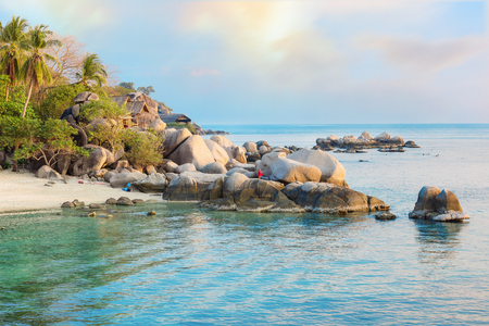 Beaches of Thailand. Empty morning beach with girl on rocks