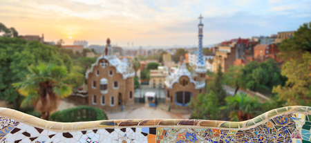 Park Guell in Barcelona. Defocused view to entrace houses with mosaics on foreground
