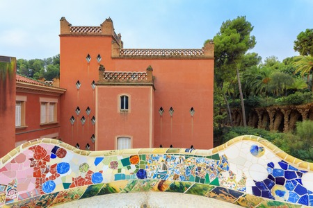 Park Guell in Barcelona. View on red pavilion with mosaics on foreground Stock Photo