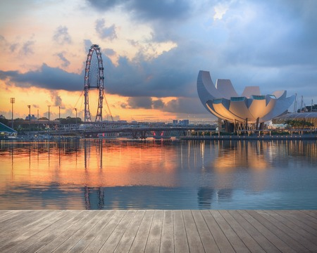 Singapore, Republic of Singapore - May 4, 2016: Panorama of Marina Bay with Artscience lotus flower museum, Flyer observation wheel and Helix bridge at sunset with decks on foreground Editorial