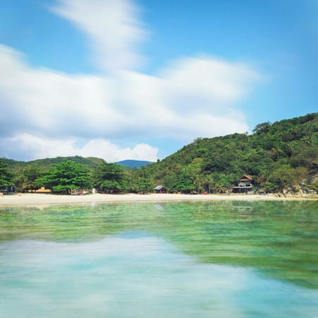 Phangan beach with white sand and tall palms shot from water Stock Photo