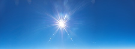 sky background with sun beams on bright blue sky