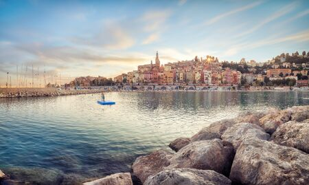 Public beach of Menton old town at sunset Banco de Imagens