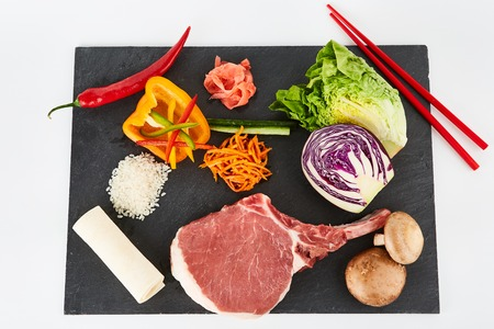australian beef cow: Raw steak served with vegetables and forest mushrooms on black metal cutting board Stock Photo