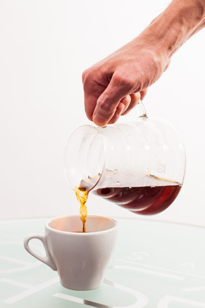 coffee filter: preparation of a coffee filter, cup on the table, coffee pot in hand Stock Photo