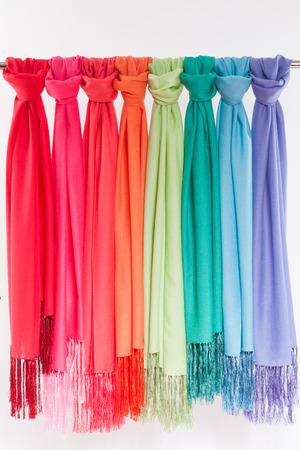 trabajo manual: bufandas de colores y cuadros que cuelgan sobre un fondo blanco