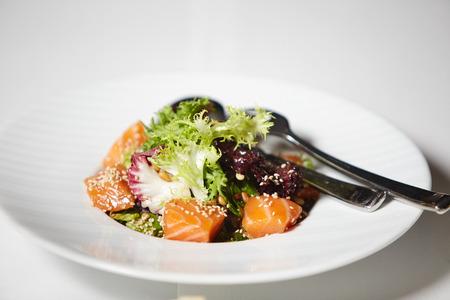 smoked salmon frash salad on white plate