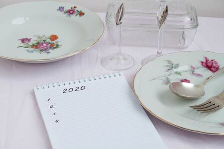 Plans for 2020 write in notebook notebook lies on the table near are worth beautiful festive plates a fork and spoon 版權商用圖片