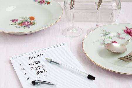 Plans for 2020 write in notebook notebook lies on the table near are worth beautiful festive plates a fork and spoon