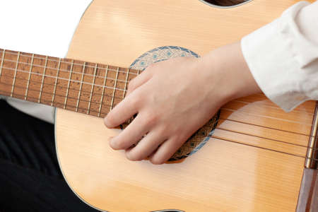 Close up of a girl's hand on the strings of a guitar.